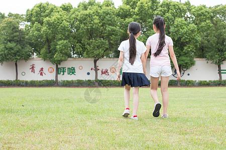 在操场草坪一起玩耍奔跑的小学生图片
