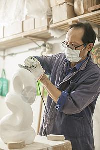 匠人石匠师傅在用工具打磨石料图片