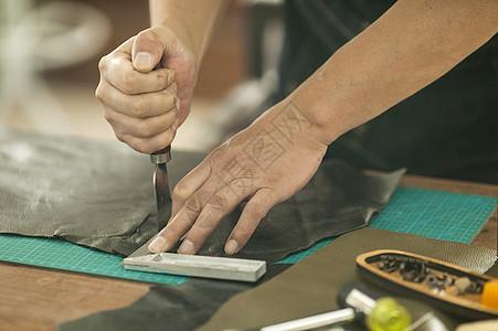 皮匠师傅专注的在裁切皮革图片