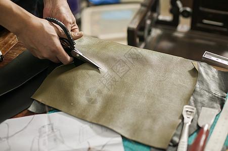 皮匠在专注的裁剪皮革图片