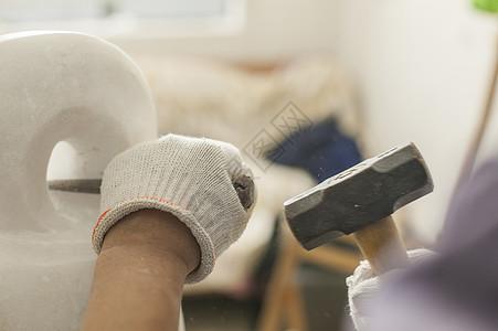 专注的石匠雕刻师傅在雕刻作品图片