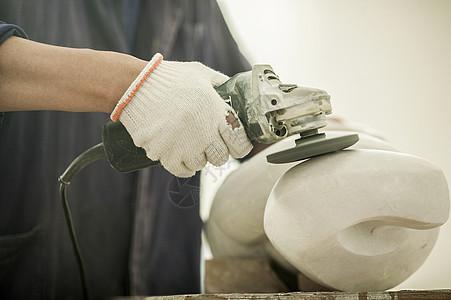 专注的石匠师傅在打磨石雕图片