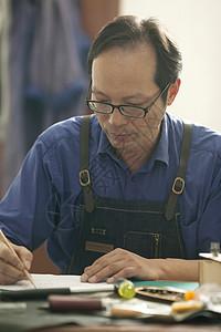 皮匠师傅在画手工定制品草图图片