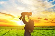 夕阳下的田间母婴图片