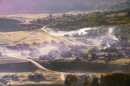 新疆阿勒泰禾木村庄晨雾炊烟图片