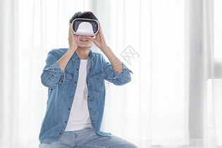 年轻男子在客厅体验虚拟现实VR眼镜图片