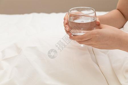 早起起床拿着水杯喝水特写图片