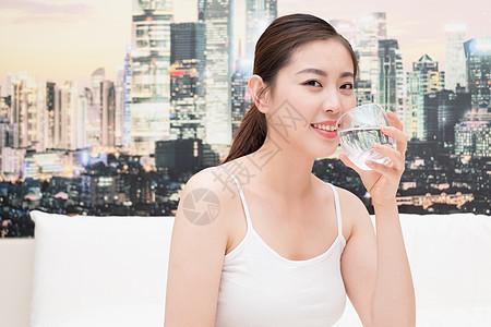 坐在床上喝水的年轻美女图片