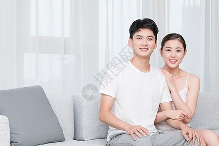 年轻情侣恩爱地坐在客厅沙发图片