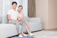 年轻情侣恩爱地坐在客厅沙发500609981图片