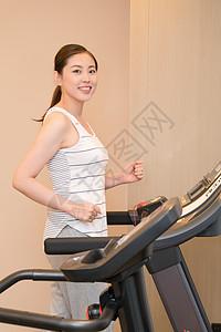 年轻女子在跑步机上运动跑步图片