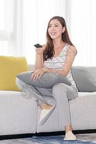 年轻女性在沙发上使用遥控器图片