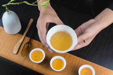手端着白色茶碗品茶图片