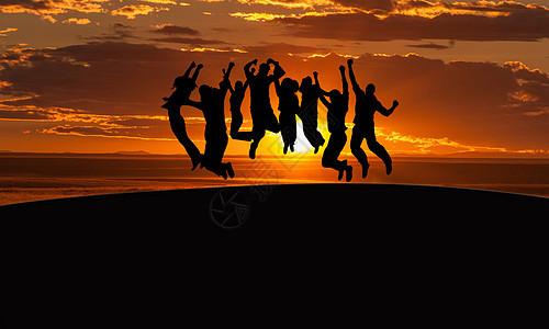 夕阳下爬上山顶欢呼雀跃的人图片
