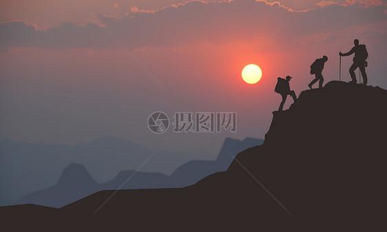 夕阳下爬山爱好者成功爬上山的顶峰图片