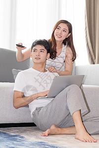 年轻夫妻一起在客厅沙发上看电视图片