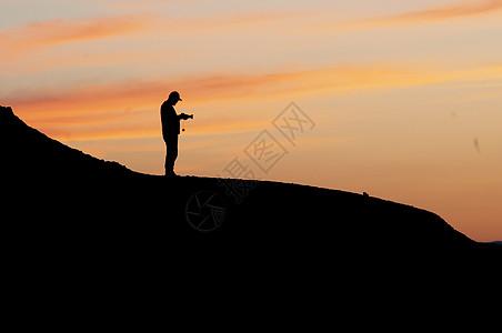 新疆克拉玛依魔鬼城摄影人日落剪影图片