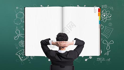 黑板前阅读笔记的人图片