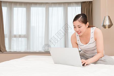 坐在床上玩电脑休闲放松的年轻女性图片