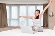 边玩电脑边舒展身体的年轻美女图片