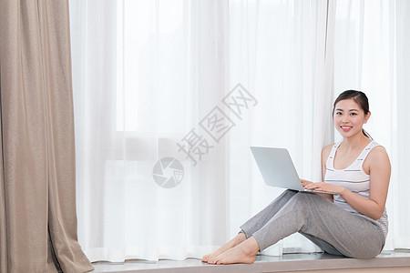 坐在客厅窗台使用笔记本电脑的美女图片