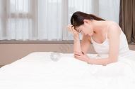 年轻女性失眠头痛坐在床上图片