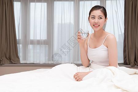 早起睡前坐在床上喝水的美女图片