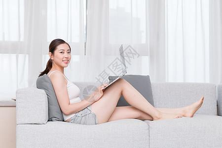 坐在沙发上使用笔记本电脑的年轻女性图片