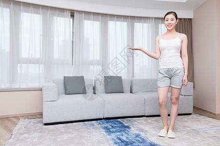 居家休闲美女站在客厅做展示动作图片