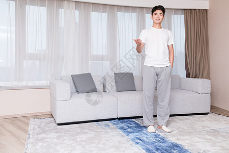 居家男子站在客厅做展示动作图片