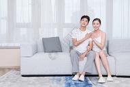 年轻夫妻坐在客厅沙发上图片