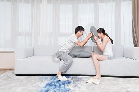 年轻情侣夫妻在客厅抢枕头图片