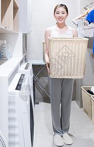 抱着洗衣篮洗衣服做家务的年轻女性图片