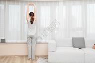 年轻女性在客厅窗前伸展运动图片