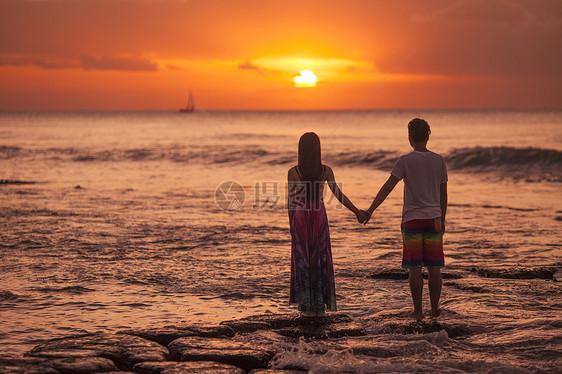 旅行中浪漫情侣在海中看夕阳图片