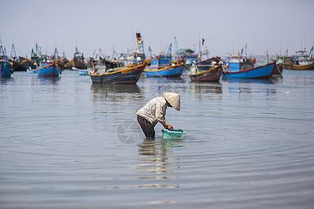 海边渔民在专注的劳作图片
