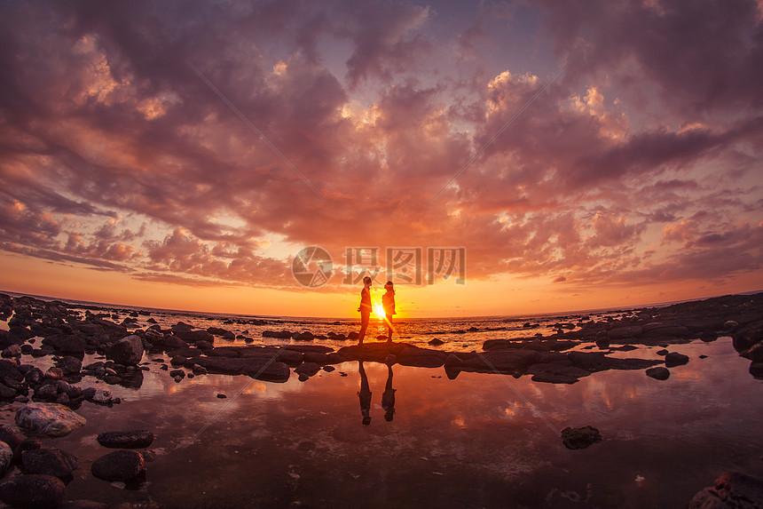 旅行中情侣在夕阳下浪漫对视图片