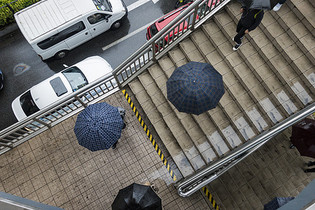 城市里雨天人们打着伞图片