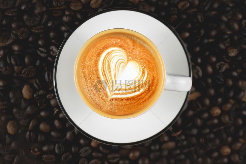 拉花咖啡杯与咖啡豆图片