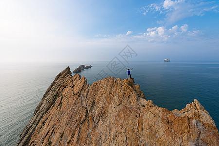 站在海边礁石上的人物背影图片