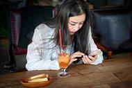 咖啡厅玩手机的年轻女生图片