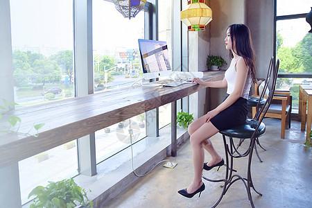 窗边玩电脑的年轻女性图片
