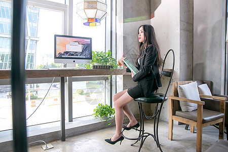 窗前看书的商务女性图片