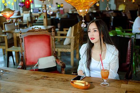 咖啡厅玩手机的年轻女性图片