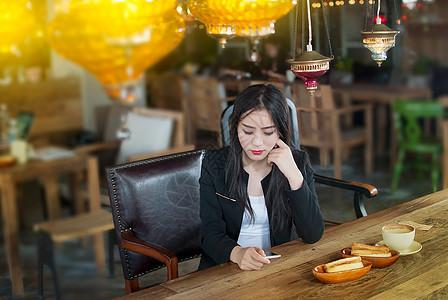 咖啡馆看手机的商务女性图片