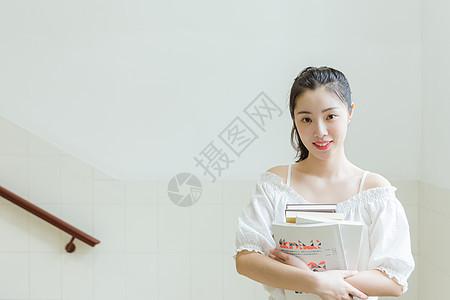 大学教学楼内女生抱着书本图片