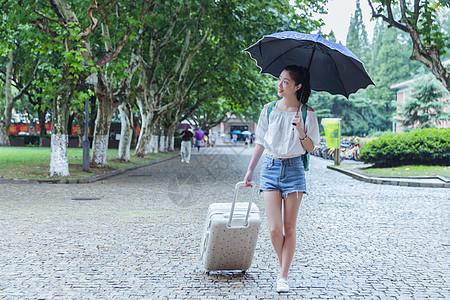 下雨天女生拉旅行箱张望图片