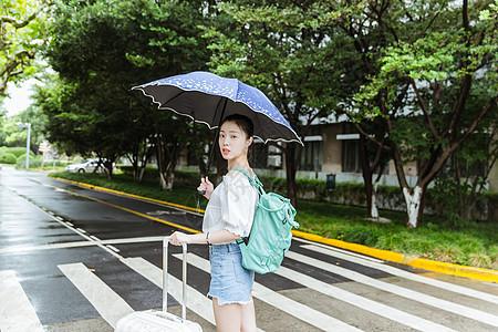下雨天女生拉旅行箱回头图片