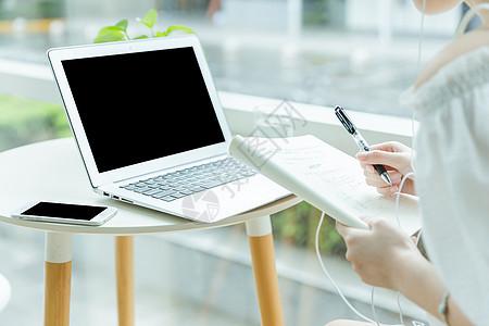 咖啡馆女生使用电脑写作特写图片