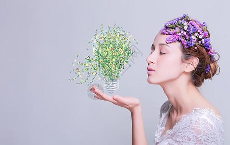 女人手托蝴蝶花卉绿叶灯泡图片